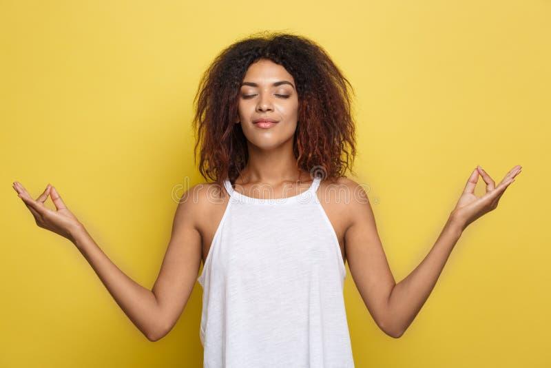 Stående av den härliga lugna unga afrikansk amerikansvartkvinnlign med praktiserande yoga för afro- frisyr inomhus som mediterar royaltyfria bilder