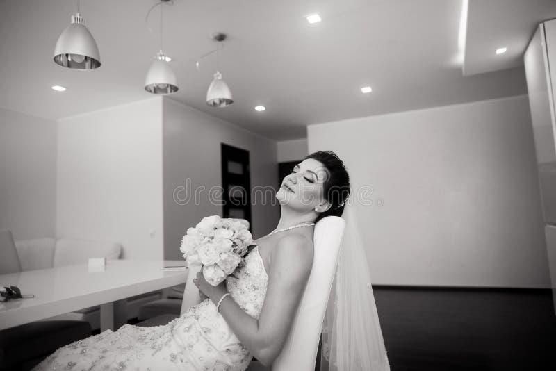 St?ende av den h?rliga lyckliga bruden som sitter p? soffan royaltyfria foton