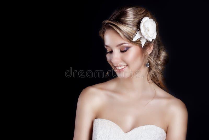 Stående av den härliga lyckliga försiktiga kvinnabruden i ett vitt för salongbröllop för bröllopsklänning c härligt hår med vita  royaltyfria bilder