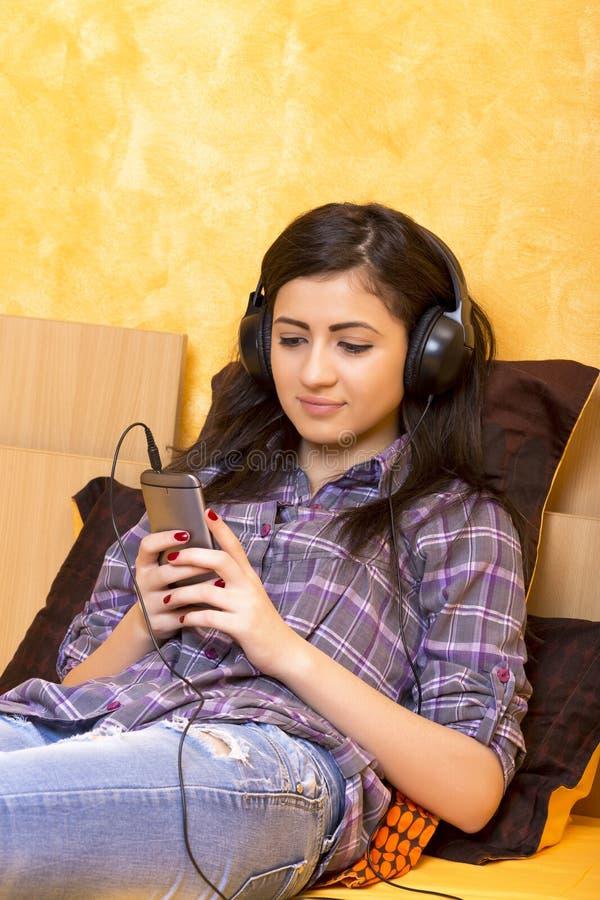 Stående av den härliga lyckliga flickan som ligger på en säng med hörlurar arkivbilder