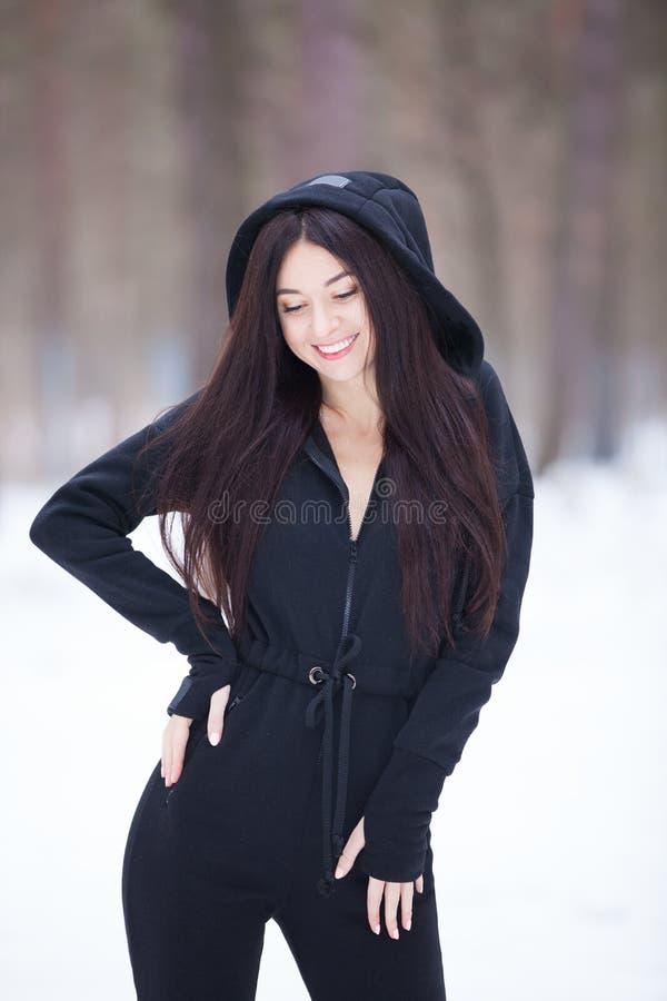 Stående av den härliga lyckliga stilfulla kvinnan i overaller som går på livsstilen för kvinna för vinterskogmode Kvinnastil som  royaltyfri foto