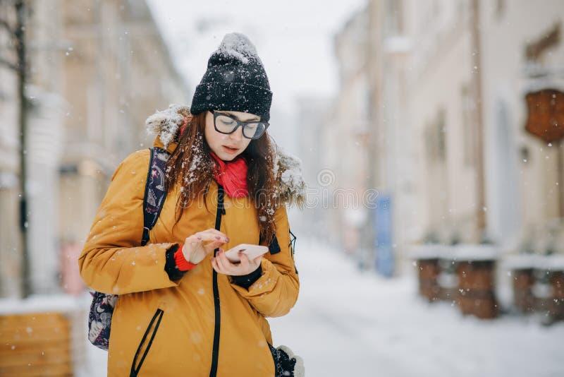 Stående av den härliga lyckliga unga kvinnan med smartphonen över julljus i vinter royaltyfri fotografi