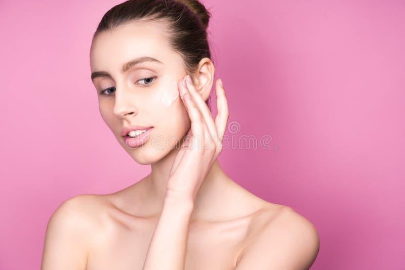 Stående av den härliga modelldamen med det naturliga sminket som applicerar kräm på hennes framsida arkivfoton