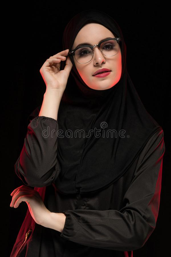 Stående av den härliga moderiktiga unga muslimkvinnan som bär svart hijab och exponeringsglas som modernt östligt posera för mode royaltyfri foto