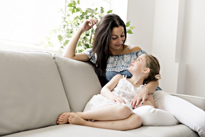 Stående av den härliga modern och hennes lilla dottern som tillsammans sitter på soffan royaltyfria bilder