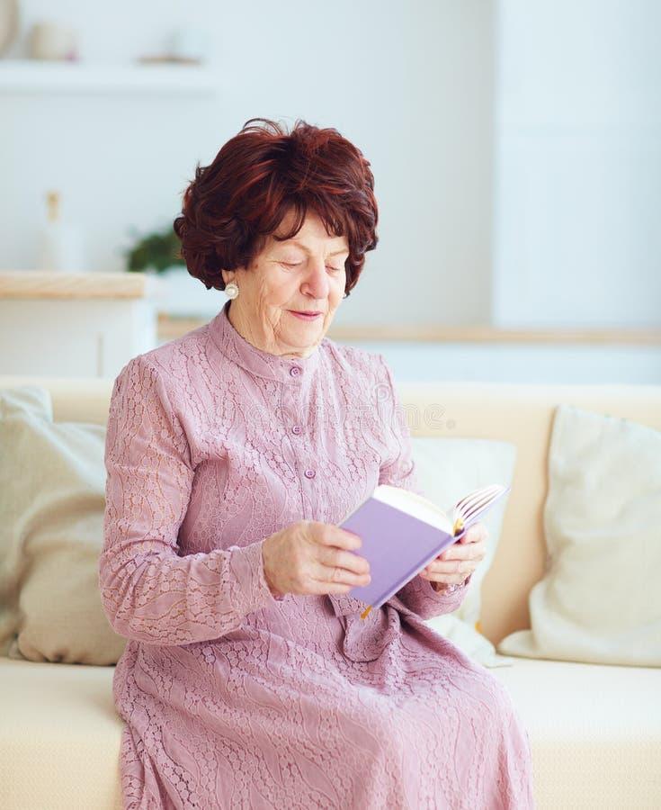 Stående av den härliga mogna kvinnan 80 år gammalt sammanträde på soffan hemma som läser en bok arkivbilder