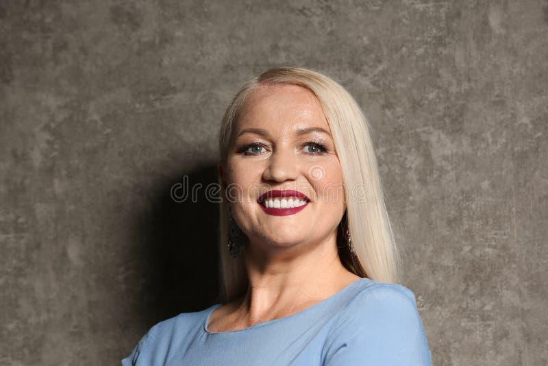 Stående av den härliga mogna kvinnan på grå färger royaltyfri foto