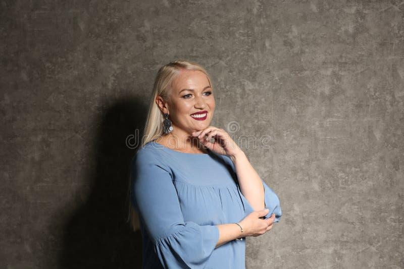 Stående av den härliga mogna kvinnan på grå färger royaltyfria bilder