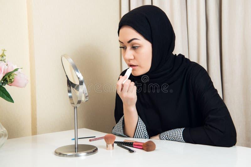 Stående av den härliga muslim kvinnan med hijab som applicerar läppstift royaltyfri bild