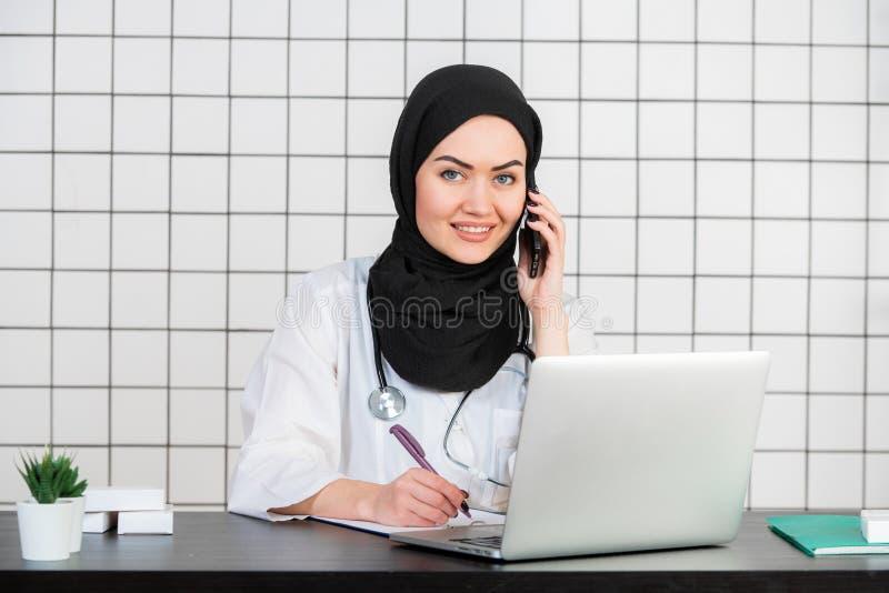 Stående av den härliga muslim kvinnliga doktorn som använder mobiltelefonen royaltyfria bilder