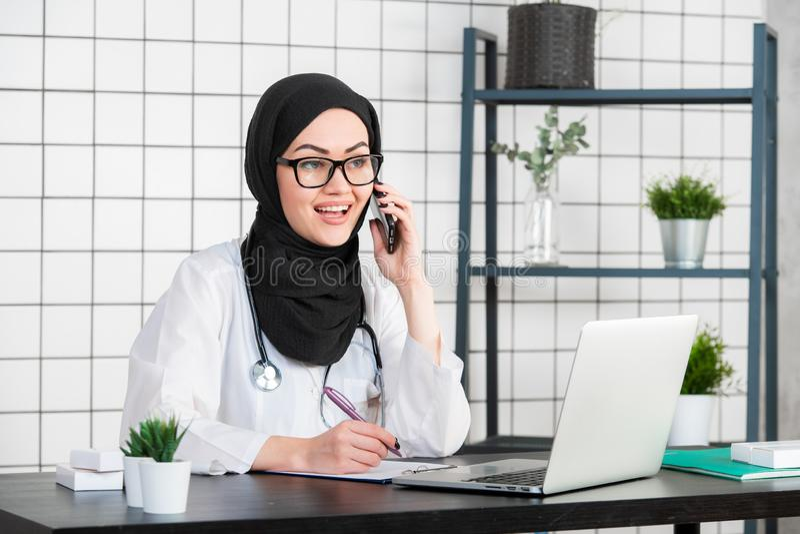 Stående av den härliga muslim kvinnliga doktorn som använder mobiltelefonen royaltyfri bild