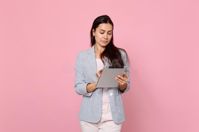 Stående av den härliga nätta unga kvinnan i randigt omslag genom att använda minnestavlaPCdatoren som isoleras på den rosa pastel royaltyfri foto