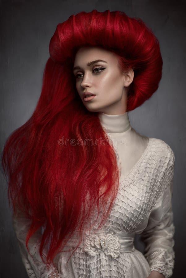 Stående av den härliga röda haired kvinnan i den vita tappningklänningen royaltyfri foto