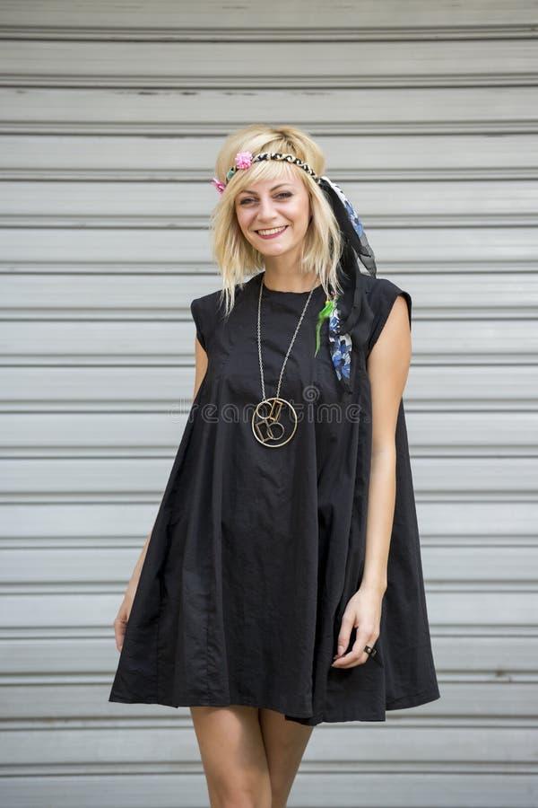 Stående av den härliga seende långa flickaklänningen för blont hår som hippie framme av bakgrund för glidningsdörrar arkivbild