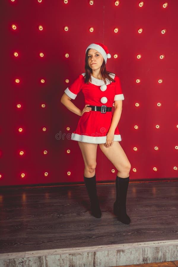 Stående av den härliga sexiga flickan som bär Santa Claus kläder på röd bakgrund arkivfoton