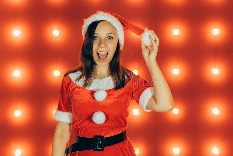 Stående av den härliga sexiga flickan som bär Santa Claus kläder på röd bakgrund fotografering för bildbyråer