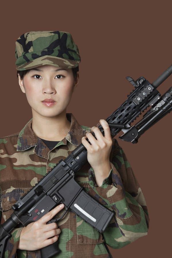 Stående av den härliga soldaten för barnUSA Marine Corps med geväret för anfall M4 över brun bakgrund arkivfoton