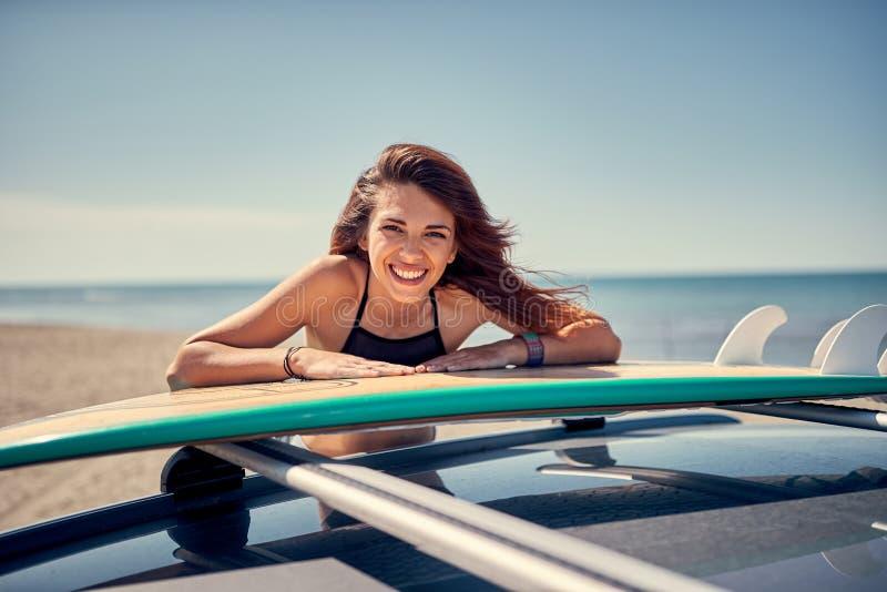 Stående av den härliga surfareflickan på stranden som får klar för fotografering för bildbyråer