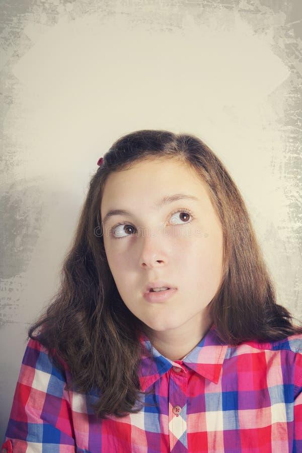 Stående av den härliga tonårs- flickan som tänker och ser upp arkivbilder