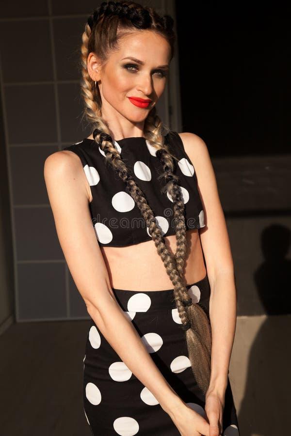 Stående av den härliga trendiga kvinnan med flätade trådar i klänning royaltyfri foto
