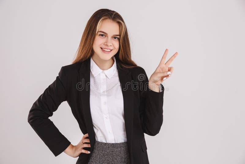Stående av den härliga unga affärskvinnan med ett fredtecken på grå bakgrund kopiera avstånd arkivbild