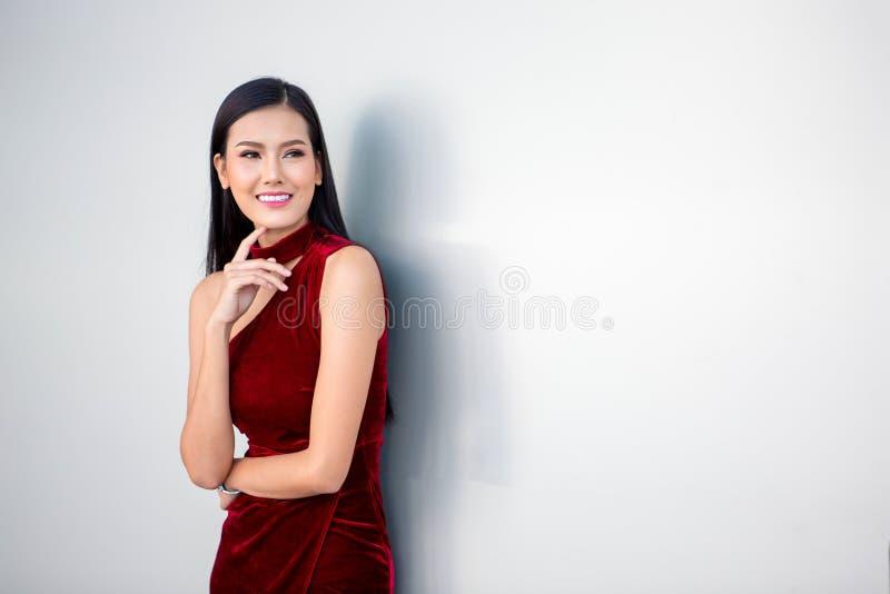 Stående av den härliga unga asiatiska kvinnan i en röd klänning som poserar med handen på hakan och ler som ser bort på vit bakgr fotografering för bildbyråer