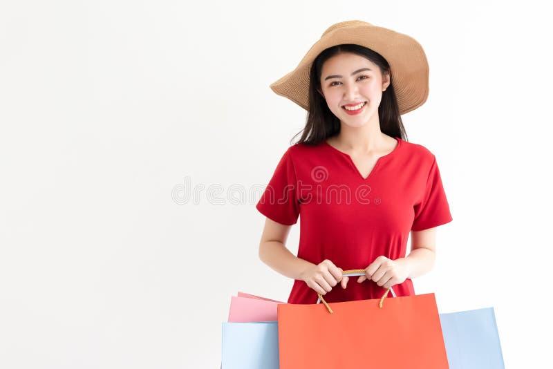 Stående av den härliga unga asiatiska kvinnan som bär den röda långa klänningen som rymmer shoppingpåsar isolerade över vit bakgr arkivfoto