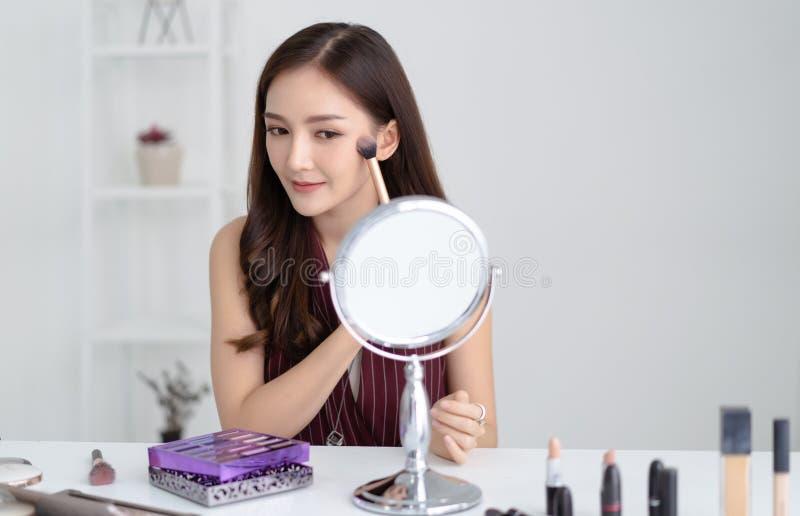 Stående av den härliga unga asiatiska kvinnan som gör sminket som ser i spegeln och applicerar skönhetsmedlet med en borste natur arkivfoton