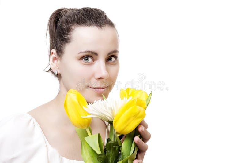 Stående av den härliga unga attraktiva brunettkvinnan med vårbuketten av tulpan för gula och vita blommor royaltyfri bild