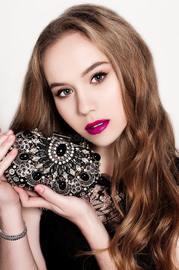Stående av den härliga unga blonda flickan i den svarta klänningen som holfing hennes handväska Modefoto, slut upp arkivbild