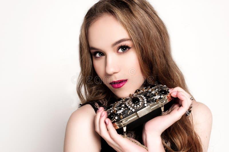 Stående av den härliga unga blonda flickan i den svarta klänningen som holfing hennes handväska Modefoto, slut upp royaltyfria bilder