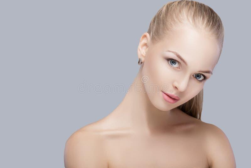 Stående av den härliga unga blonda kvinnan med blåa ögon på grå bakgrund gör ren flickahud arkivfoton
