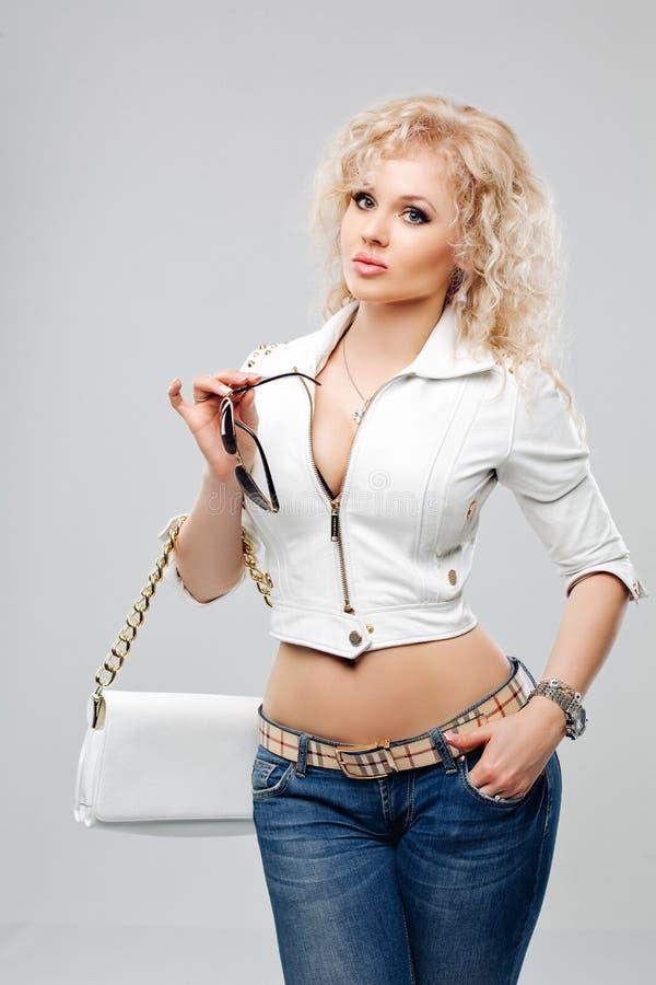 Stående av den härliga unga blonda kvinnan med lockigt hår Flickan bar ett omslag för vitt läder, jeans och royaltyfri fotografi