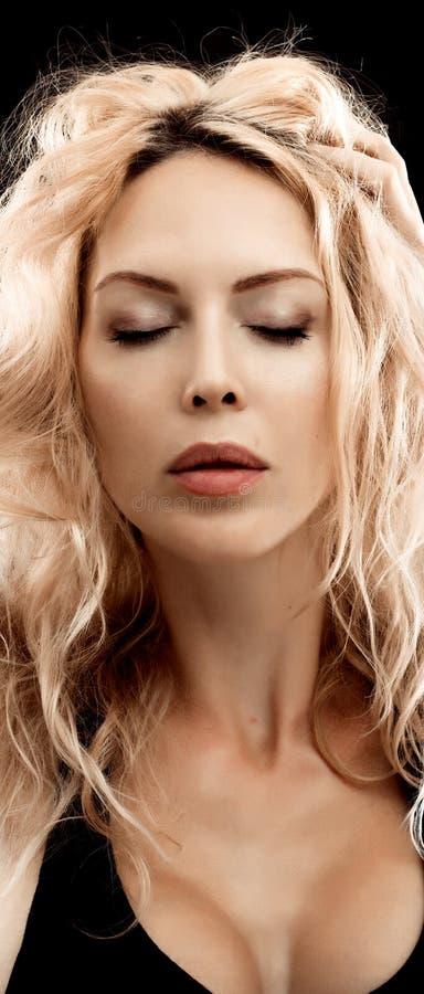 Stående av den härliga unga blonda kvinnan på svart fotografering för bildbyråer