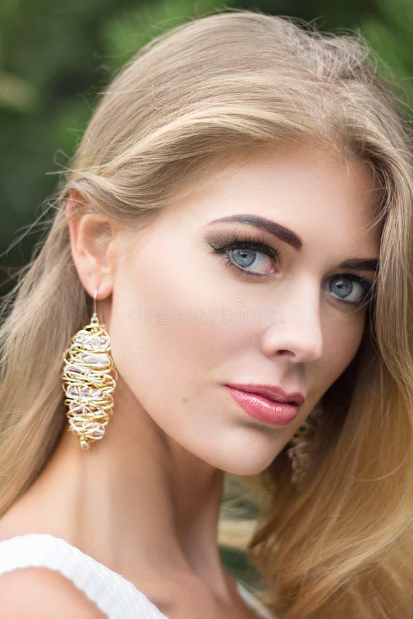 Stående av den härliga unga blonda kvinnan utomhus royaltyfri bild