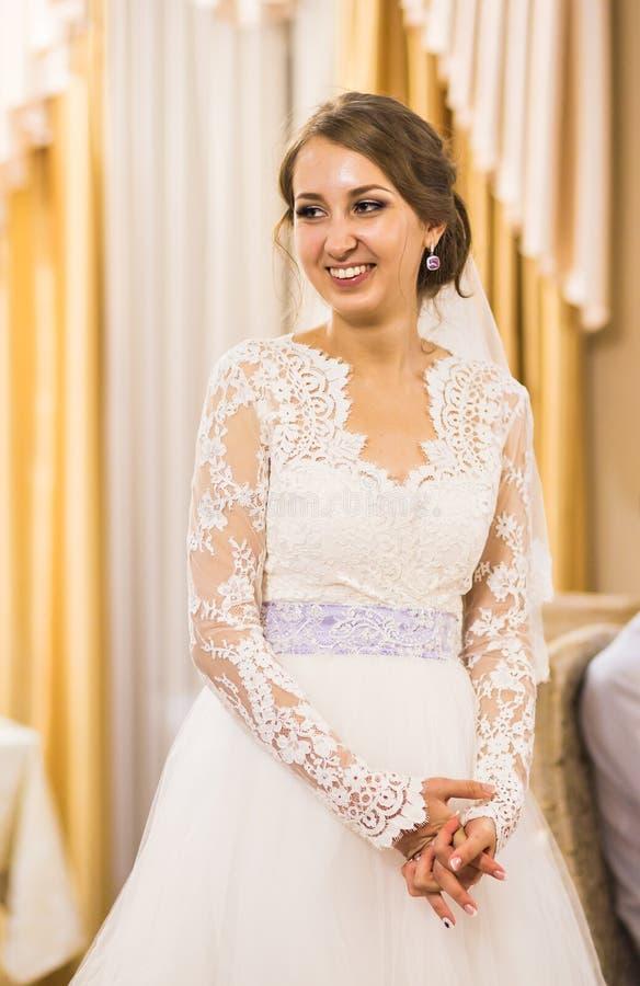 Stående av den härliga unga bruden i elegant vit klänning inomhus royaltyfria foton