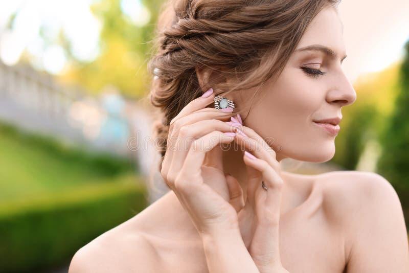 Stående av den härliga unga bruden med det eleganta örhänget utomhus arkivbilder
