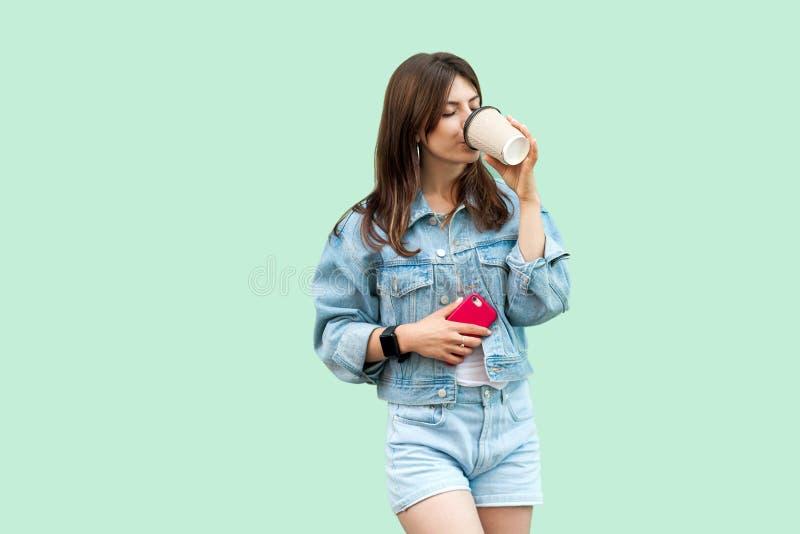 Stående av den härliga unga brunettkvinnan, i tillfälligt anseende och att rymma den disponibla koppen, att dricka och vila för g fotografering för bildbyråer