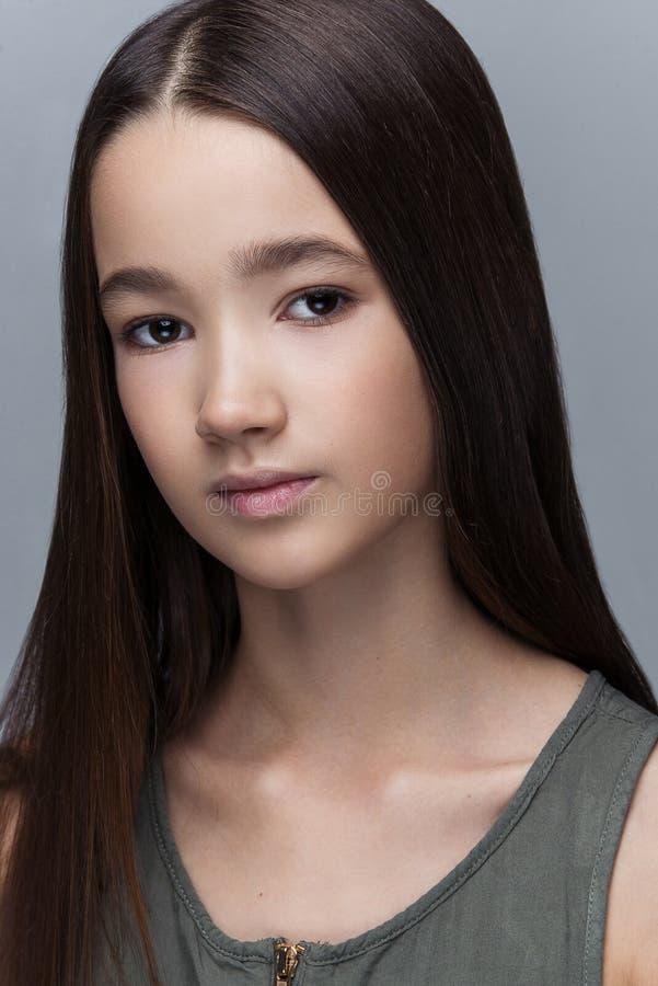 Stående av den härliga unga flickan som poserar i studio fotografering för bildbyråer
