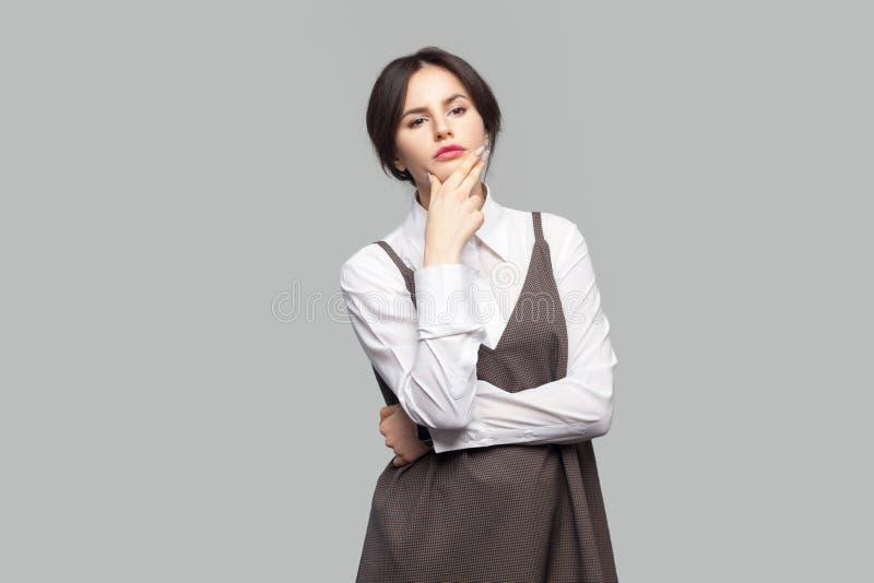 Stående av den härliga unga kvinnan för allvarlig fråga i den vita skjortan och brunt förkläde med makeup, samlat håranseende som royaltyfri fotografi
