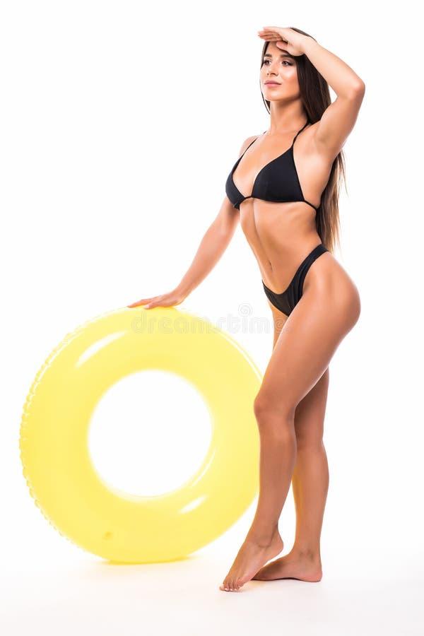 Stående av den härliga unga kvinnan i bikinin som spelar med flötet som isoleras på vit bakgrund royaltyfria foton