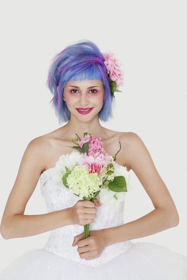 Stående av den härliga unga kvinnan i bröllopsklänning med färgat hår mot grå bakgrund fotografering för bildbyråer