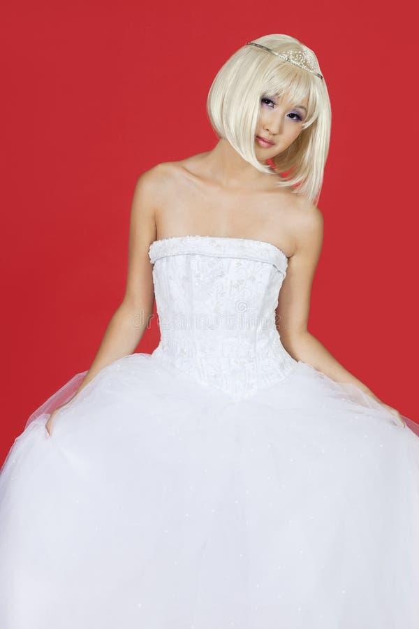 Stående av den härliga unga kvinnan i bröllopsklänninganseende mot röd bakgrund royaltyfria bilder