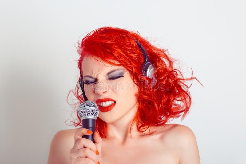 Stående av den härliga unga kvinnan i hörlurar som sjunger in i en mikrofon arkivfoton
