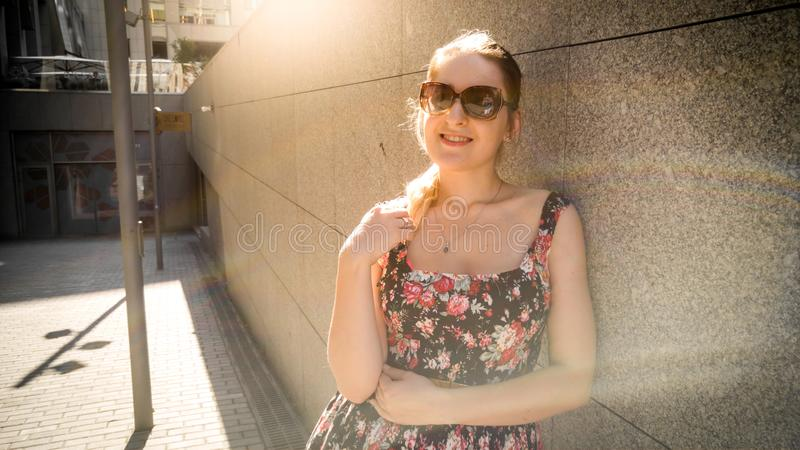 Stående av den härliga unga kvinnan i den korta klänningen som lutar mot stenväggen på stadsgatan och in camera ser arkivbild