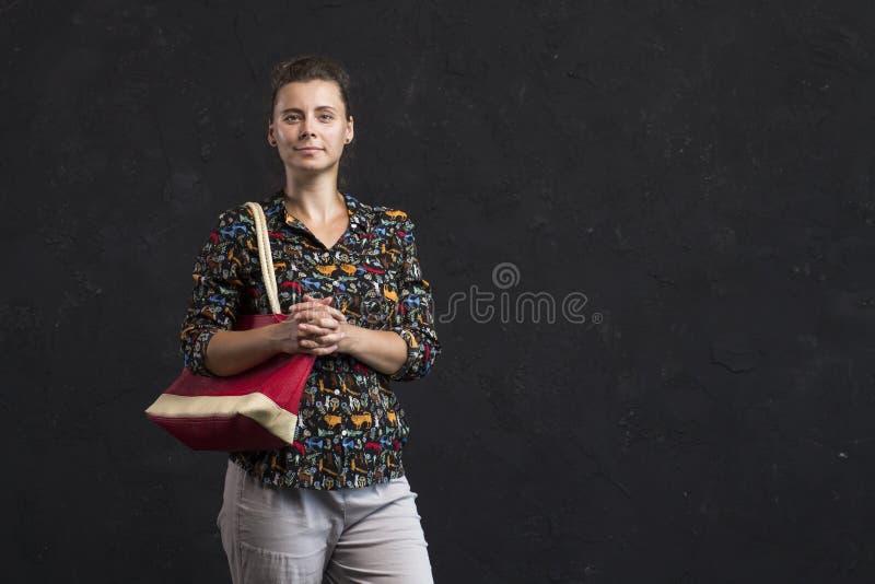 Stående av den härliga unga kvinnan i trendig kläder med den röda handväskan royaltyfri bild