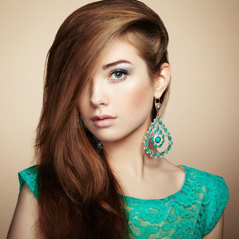 Stående av den härliga unga kvinnan med örhänget Smycken och acce arkivbild