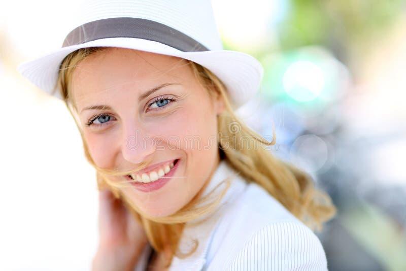 Stående av den härliga unga kvinnan med att le för hatt arkivbilder