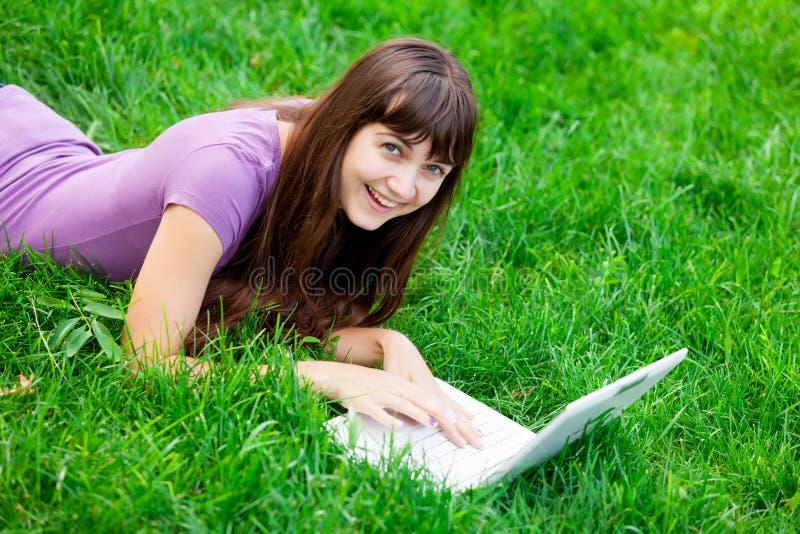 Stående av den härliga unga kvinnan med bärbara datorn som ligger på gräsplanen arkivbild
