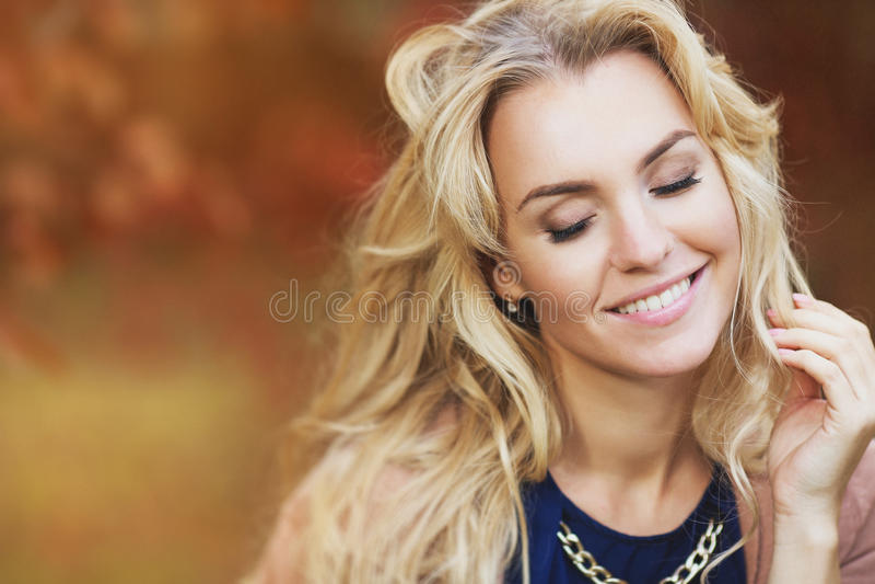 Stående av den härliga unga kvinnan med ett blont hår i höst arkivfoto